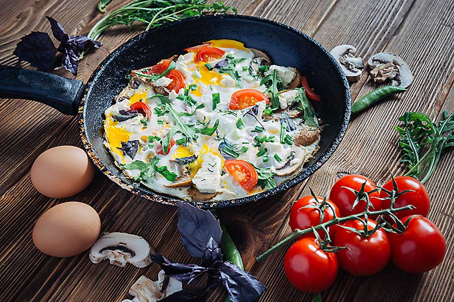 Fried eggs on a pan served with tomato, mushrooms, cheese, basil, onions and arugula.