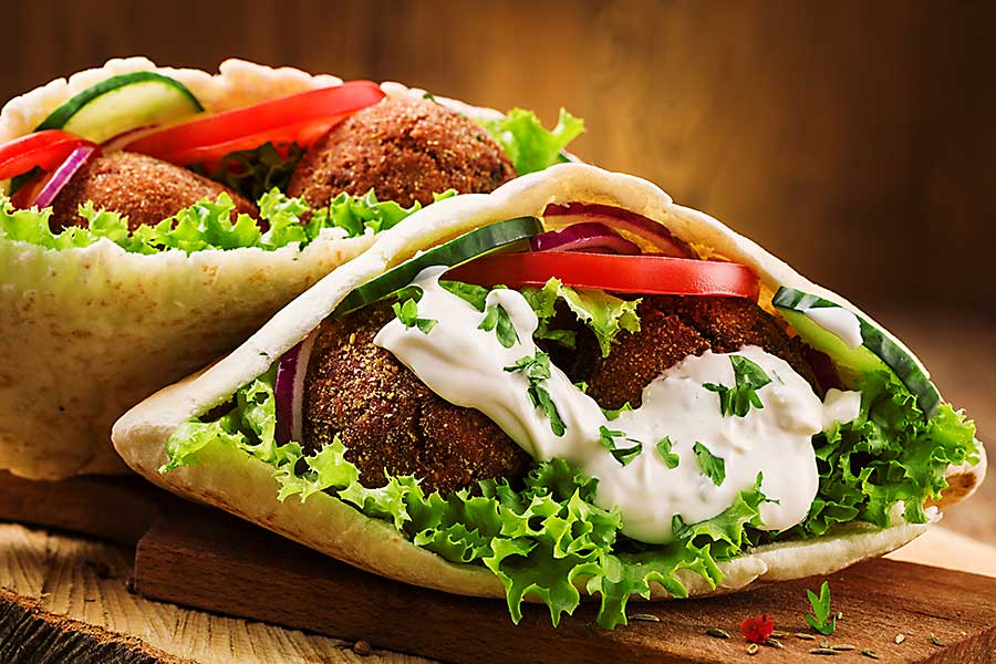 Israeli Falafel and fresh vegetables in pita bread on wooden table