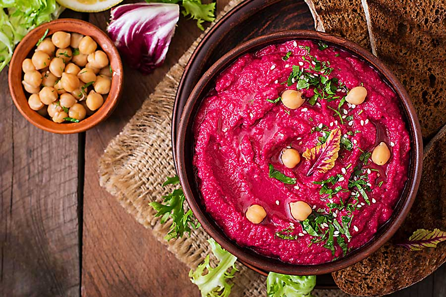 Roasted Beet Hummus with toast in a ceramic bowl