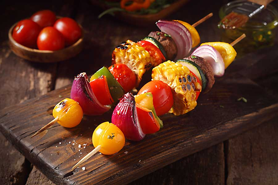 Colourful vegetarian vegetable skewers with fresh roasted or grilled sweet peppers, onion, mushroom, corn, eggplant and cherry tomatoes.