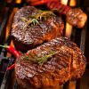 Charcoal bbq experience, red chilli peppers and grass-fed hormon free beef rump steak on the grill with garlic and rosemary