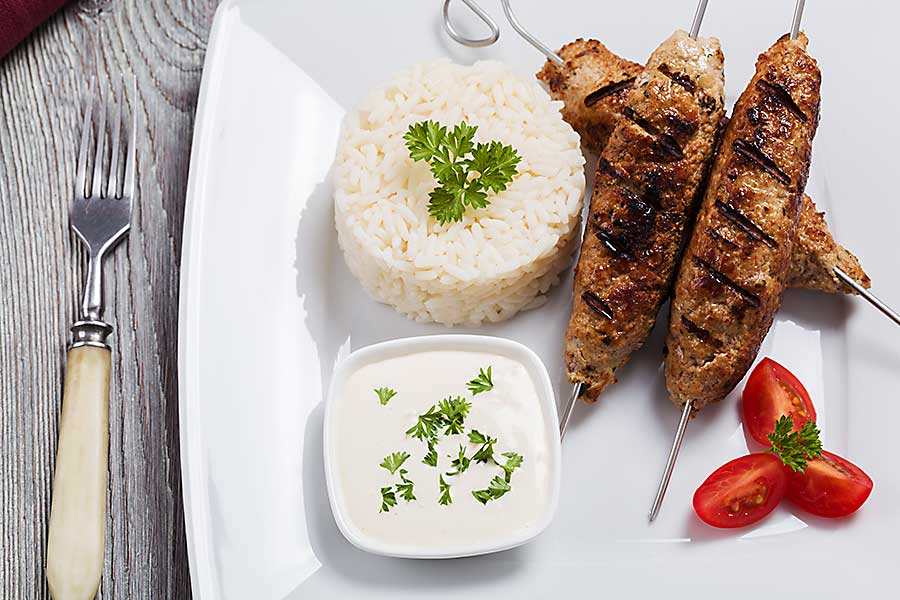 Barbecued kofta - kebeb with rice and vegetables on a plate.