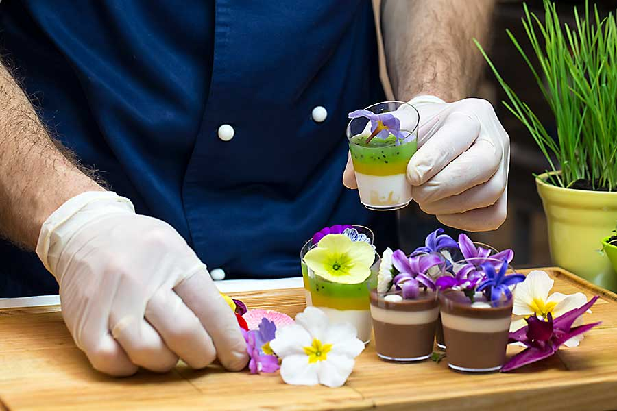 Chef prepares canapes dessert edible flowers and buds