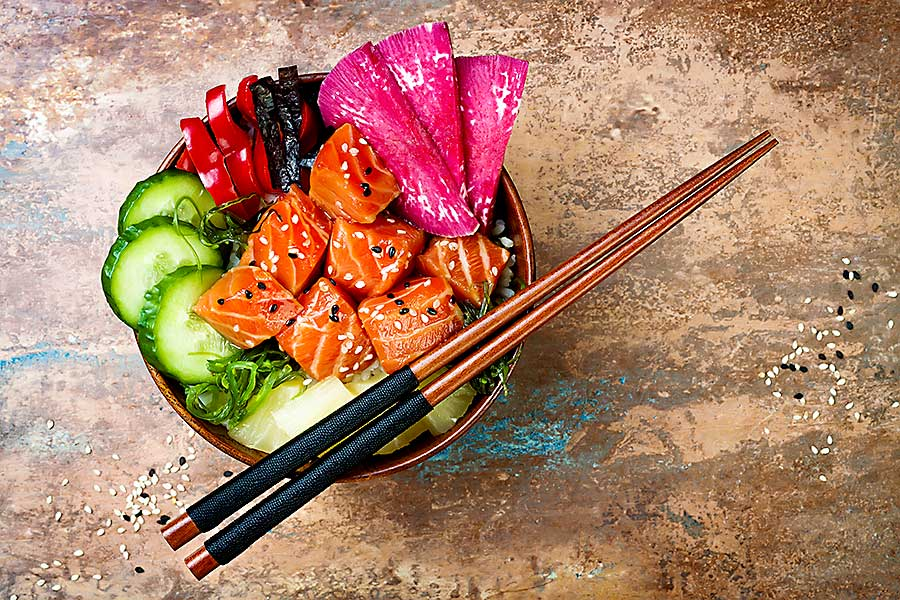 Hawaiian food - salmon poke bowl with seaweed, watermelon radish, cucumber, pineapple and sesame seeds