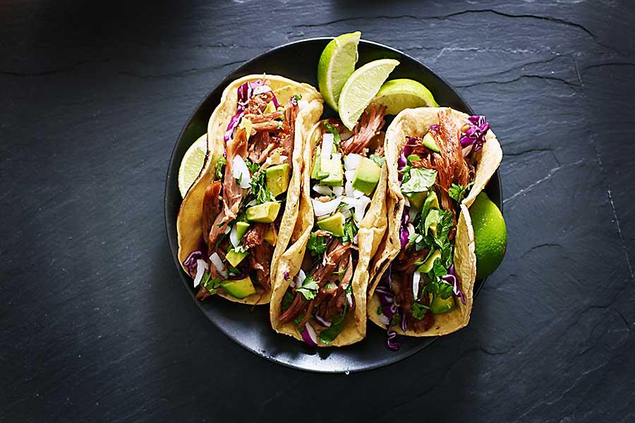 Mexican street tacos with pork carnitas, avocado, onion, cilantro, and red cabbage
