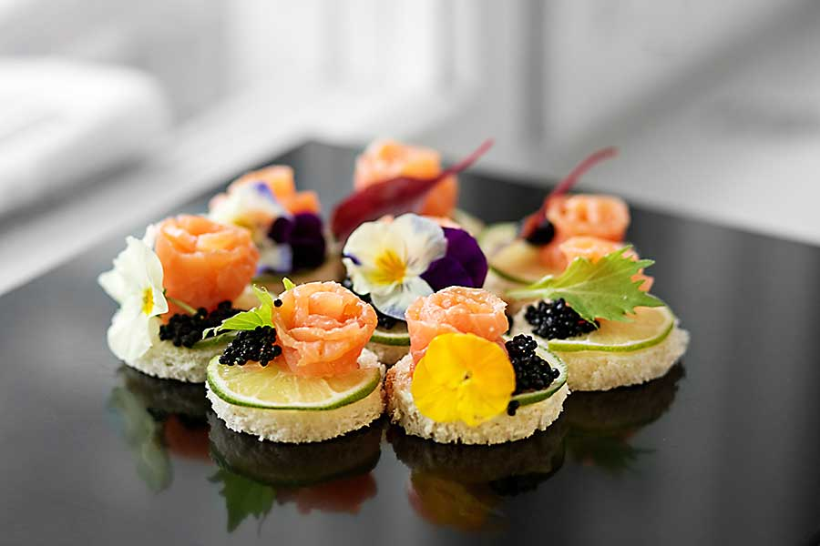 Delicious appetizer with salmon and edible flowers.